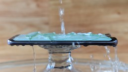 Testing waterproof mobile phone with pouring water splash over water resistant screen